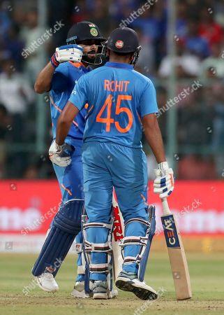 Virat Kohli, Rohit Sharma. India's captain Virat Kohli, left, congratulates teammate Rohit Sharma on scoring a century during the third one-day international cricket match between India and Australia in Bangalore, India