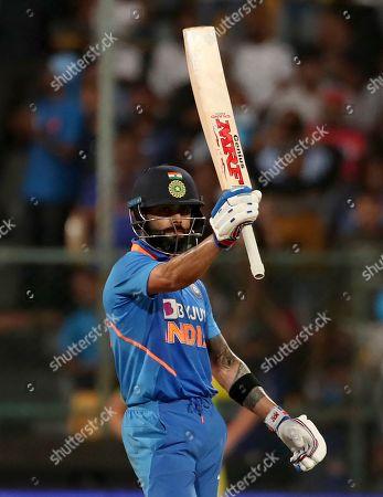 India's captain Virat Kohli raises his bat to celebrate scoring fifty runs during the third one-day international cricket match between India and Australia in Bangalore, India