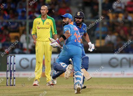 Stock Image of Ashton Agar, Virat Kohli, Rohit Sharma. Australia's Ashton Agar, left, watches as India's captain Virat Kohli, center, and Rohit Sharma run between the wickets to score during the third one-day international cricket match between India and Australia in Bangalore, India