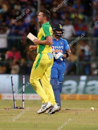 Josh Hazlewood, Virat Kohli. Australia's Josh Hazlewood, left, celebrates the dismissal of India's captain Virat Kohli, right, during the third one-day international cricket match between India and Australia in Bangalore, India