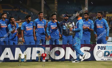 Stock Photo of India's captain Virat Kohli, third right, arrives with the winners trophy for a group photograph after their win in the third one-day international cricket match between India and Australia in Bangalore, India, . India won the series 2-1