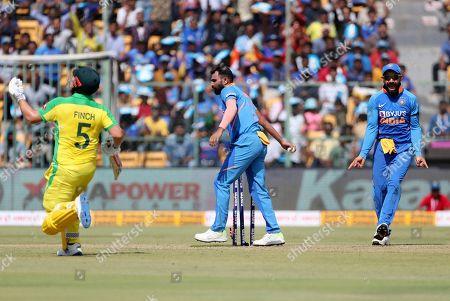 Virat Kohli, Aaron Finch, Mohammed Shami. India's captain Virat Kohli, right, celebrates the run-out of Australia's captain Aaron Finch, left, by India's Mohammed Shami, center, during the third one-day international cricket match between India and Australia in Bangalore, India