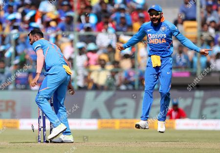 Virat Kohli, Mohammed Shami. India's captain Virat Kohli, right, celebrates the run-out of Australia's captain Aaron Finch by teammate Mohammed Shami, left, during the third one-day international cricket match between India and Australia in Bangalore, India