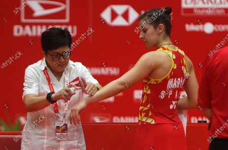 Carolina Marin of Spain  (R)  checks by a medical person during  women single's final  match against Ratchanok Intanon of Thailand (unseen) at the Daihatsu Indonesian Masters badminston tournament in Jakarta, Indonesia 19 January 2020