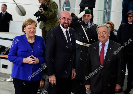 German Chancellor Angela Merkel, left, greets United Nations Secretary General Antonio Guterres, right, and European Council President Charles Michel, center, during arrivals for a conference on Libya at the chancellery in Berlin, Germany, . German Chancellor Angela Merkel hosts the one-day conference of world powers on Sunday seeking to curb foreign military interference, solidify a cease-fire and help relaunch a political process to stop the chaos in the North African nation