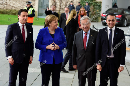 German Chancellor Angela Merkel, second left, greets from left, Italian Prime Minister Giuseppe Conte, United Nations Secretary General Antonio Guterres, and Italian Foreign Minister Luigi Di Maio during arrivals for a conference on Libya at the chancellery in Berlin, Germany, . German Chancellor Angela Merkel hosts the one-day conference of world powers on Sunday seeking to curb foreign military interference, solidify a cease-fire and help relaunch a political process to stop the chaos in the North African nation