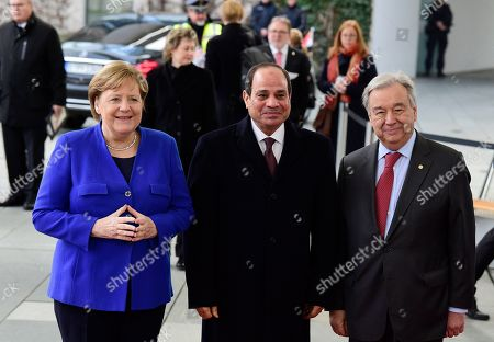 German Chancellor Angela Merkel, left, greets United Nations Secretary General Antonio Guterres, right, and Egypt's President Abdel Fattah al-Sisi, center, during arrivals for a conference on Libya at the chancellery in Berlin, Germany, . German Chancellor Angela Merkel hosts the one-day conference of world powers on Sunday seeking to curb foreign military interference, solidify a cease-fire and help relaunch a political process to stop the chaos in the North African nation