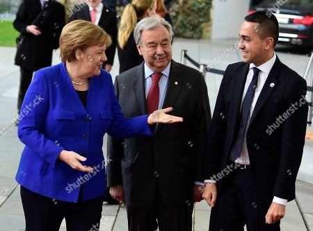 German Chancellor Angela Merkel, left, greets United Nations Secretary General Antonio Guterres, center, and Italian Foreign Minister Luigi Di Maio during arrivals for a conference on Libya at the chancellery in Berlin, Germany, . German Chancellor Angela Merkel hosts the one-day conference of world powers on Sunday seeking to curb foreign military interference, solidify a cease-fire and help relaunch a political process to stop the chaos in the North African nation