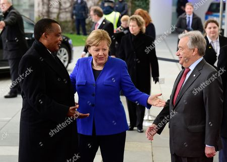 German Chancellor Angela Merkel, center, greets President of the Republic of Congo Denis Sassou Nguesso, left, during arrivals for a conference on Libya at the chancellery in Berlin, Germany, . German Chancellor Angela Merkel hosts the one-day conference of world powers on Sunday seeking to curb foreign military interference, solidify a cease-fire and help relaunch a political process to stop the chaos in the North African nation