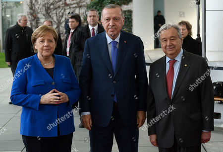 German Chancellor Angela Merkel, left, greets United Nations Secretary General Antonio Guterres, right, and Turkish President Recep Tayyip Erdogan, center, during arrivals for a conference on Libya at the chancellery in Berlin, Germany, . German Chancellor Angela Merkel hosts the one-day conference of world powers on Sunday seeking to curb foreign military interference, solidify a cease-fire and help relaunch a political process to stop the chaos in the North African nation