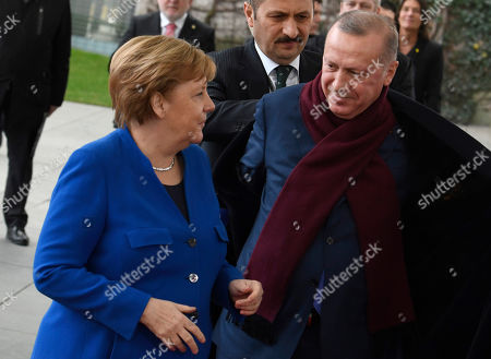 German Chancellor Angela Merkel, left, greets Turkish President Recep Tayyip Erdogan during arrivals for a conference on Libya at the chancellery in Berlin, Germany, . German Chancellor Angela Merkel hosts the one-day conference of world powers on Sunday seeking to curb foreign military interference, solidify a cease-fire and help relaunch a political process to stop the chaos in the North African nation