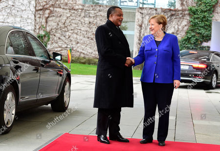 German Chancellor Angela Merkel, right, welcomes President of the Republic of Congo Denis Sassou Nguesso as he arrives for conference on Libya at the Chancellery in Berlin, . German Chancellor Angela Merkel hosts the one-day conference of world powers in Berlin to discuss efforts to broker peace in Libya