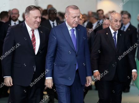 U.S. Secretary of State Mike Pompeo, left, walks with Turkish President Recep Tayyip Erdogan, center, and Algeria's President Abdelmadjid Tebboune prior to a group photo at a conference on Libya at the chancellery in Berlin, Germany, . German Chancellor Angela Merkel hosts the one-day conference of world powers on Sunday seeking to curb foreign military interference, solidify a cease-fire and help relaunch a political process to stop the chaos in the North African nation