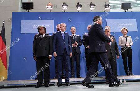 Turkish President Recep Tayyip Erdogan, center left, looks on as Egyptian President Abdel Fattah el-Sissi, center right, arrives for a group photo during a conference on Libya at the chancellery in Berlin, Germany, . German Chancellor Angela Merkel hosts the one-day conference of world powers on Sunday seeking to curb foreign military interference, solidify a cease-fire and help relaunch a political process to stop the chaos in the North African nation
