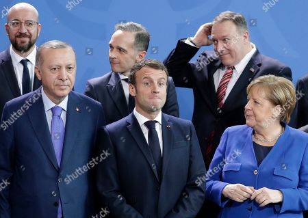 Stock Picture of German Chancellor Angela Merkel, front right, speaks with French President Emmanuel Macron, front center, during a group photo at a conference on Libya at the chancellery in Berlin, Germany, . Front left is Turkish President Recep Tayyip Erdogan. Back row left to right, European Council President Charles Michel, German Foreign Minister Heiko Maas and U.S. Secretary of State Mike Pompeo