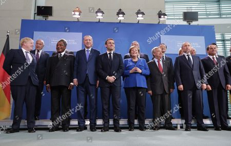 German Chancellor Angela Merkel, front center right, and French President Emmanuel Macron, front center left, pose during a group photo at a conference on Libya at the chancellery in Berlin, Germany, . Front row left to right, British Prime Minister Boris Johnson, President of the Republic Congo Denis Sassou Nguesso, Turkish President Recep Tayyip Erdogan, United Nations Secretary General Antonio Guterres, Russian President Vladimir Putin and Egyptian President Abdel Fattah el-Sissi
