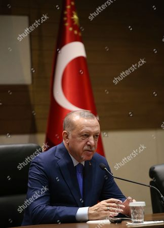 "Turkey's President Recep Tayyip Erdogan speaks to the media before traveling to Berlin for a summit on Libya, in Istanbul, . Erdogan expressed doubt Friday that Khalifa Hifter, the head of the self-styled Libyan National Army, would abide by the cease-fire. ""This man is not a trust-worthy man,"" he told reporters in Istanbul"