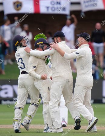 Stock Image of England's wicket keeper Jos Buttler, left, celebrates with Ollie Pope, 2nd left, after taking a catch to dismiss Rassie van der Dussen of South Africa during day four of the third cricket test between South Africa and England in Port Elizabeth, South Africa