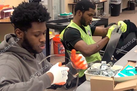 Stock Picture of Nicholas Thomas, left, and Joe Wright, right, prepare school safety signs as part of the AmeriCorps Urban Safety Program at Wayne State University's Center for Urban Studies. Volunteers will post the signs and also help board up vacant houses Monday near a Detroit school as part of an annual project commemorating the Rev. Martin Luther King Jr's birthday and the federal holiday