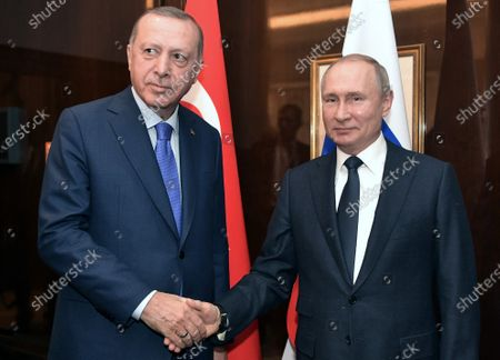 Turkish President Recep Tayyip Erdogan (L) and Russian President Vladimir Putin shake hands during their meeting prior a Peace summit on Libya in Berlin, Germany, 19 January 2020. By means of the 'Berlin Process', German government seeks to support the peace efforts of the United Nations (UN) to bring about an end to the conflict in Libya. Following the renewed outbreak of hostilities in April 2019, UN presented a plan to stop further military escalation and resume an intra-Libyan process of reconciliation.