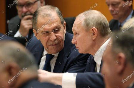 Stock Photo of Russian President Vladimir Putin (C) and Russian Foreign Minister Sergei Lavrov (L) attend the main session  for the International Libya Conference in Berlin, Germany, 19 January 2020. By means of the 'Berlin Process', German government seeks to support the peace efforts of the United Nations (UN) to bring about an end to the conflict in Libya. Following the renewed outbreak of hostilities in April 2019, UN presented a plan to stop further military escalation and resume an intra-Libyan process of reconciliation.