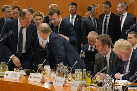 Russian President Vladimir Putin (C), Russian Foreign Minister Sergei Lavrov (L), French President Emmanuel Macron (behind Putin) and British Prime Minister Boris Johnson (R) attend the main session  for the International Libya Conference in Berlin, Germany, 19 January 2020. By means of the 'Berlin Process', German government seeks to support the peace efforts of the United Nations (UN) to bring about an end to the conflict in Libya. Following the renewed outbreak of hostilities in April 2019, UN presented a plan to stop further military escalation and resume an intra-Libyan process of reconciliation.