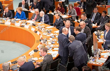 Stock Image of (center L-R) Russian President Vladimir Putin, acting Russian foreign minister Sergei Lavrov, French President Emmanel Macron, French Foreign Minister Jean-Yves Le Drian talk at the International Libya Conference in Berlin, Germany, 19 January 2020. By means of the 'Berlin Process', German government seeks to support the peace efforts of the United Nations (UN) to bring about an end to the conflict in Libya. Following the renewed outbreak of hostilities in April 2019, UN presented a plan to stop further military escalation and resume an intra-Libyan process of reconciliation.