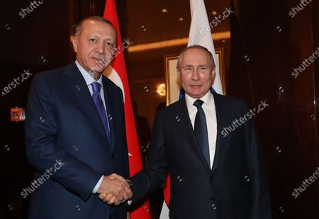 A handout photo made available by the Turkish President Press Office shows Turkish President Recep Tayyip Erdogan (L) and Russian President Vladimir Putin shake hands as they meet for a bilateral on the sidelines of the International Libya Conference in Berlin, Germany, 19 January 2020. By means of the 'Berlin Process', German government seeks to support the peace efforts of the United Nations (UN) to bring about an end to the conflict in Libya. Following the renewed outbreak of hostilities in April 2019, UN presented a plan to stop further military escalation and resume an intra-Libyan process of reconciliation.