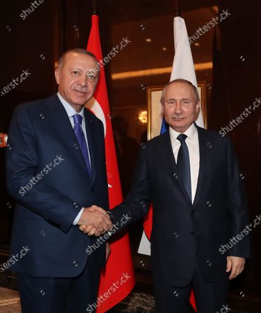 Stock Picture of A handout photo made available by the Turkish President Press Office shows Turkish President Recep Tayyip Erdogan (L) and Russian President Vladimir Putin shake hands as they meet for a bilateral on the sidelines of the International Libya Conference in Berlin, Germany, 19 January 2020. By means of the 'Berlin Process', German government seeks to support the peace efforts of the United Nations (UN) to bring about an end to the conflict in Libya. Following the renewed outbreak of hostilities in April 2019, UN presented a plan to stop further military escalation and resume an intra-Libyan process of reconciliation.