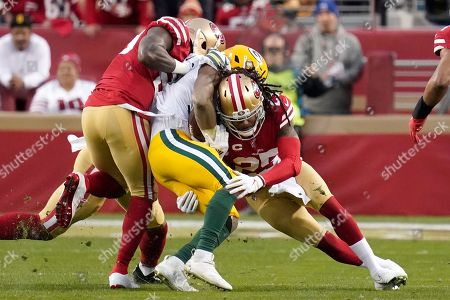 Green Bay Packers running back Aaron Jones, center, is tackled by San Francisco 49ers strong safety Jaquiski Tartt, left, and cornerback Richard Sherman during the first half of the NFL NFC Championship football game, in Santa Clara, Calif