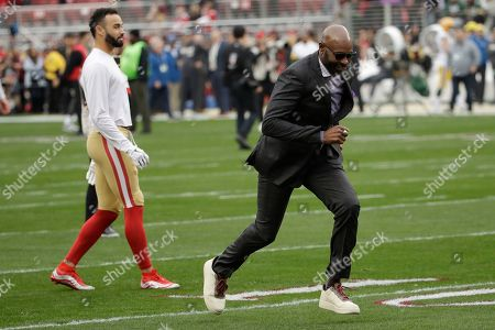 Former San Francisco 49ers wide receiver Jerry Rice, right, runs on the field in front of wide receiver Dante Pettis before the NFL NFC Championship football game between the 49ers and the Green Bay Packers, in Santa Clara, Calif