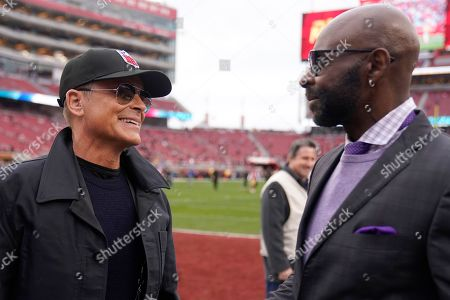 Actor Rob Lowe, left, talks with former wide receiver Jerry Rice before the NFL NFC Championship football game between the San Francisco 49ers and the Green Bay Packers, in Santa Clara, Calif