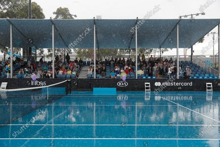 Tennis fans wait for the rain to abate during the women's singles first round match between Petra Martic of Croatia and Christina McHale of USA at the Australian Open Grand Slam tennis tournament in Melbourne, Australia, 20 January 2020.