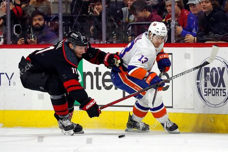 Stock Picture of Carolina Hurricanes' Jordan Staal (11) and New York Islanders' Mathew Barzal (13) vie for the puck during the third period of an NHL hockey game in Raleigh, N.C