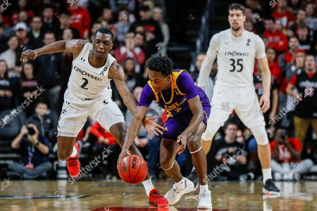 Tristen Newton, Keith Williams. East Carolina's Tristen Newton, center, and Cincinnati's Keith Williams, left, battle for a loose ball during the first half of an NCAA college basketball game, in Cincinnati