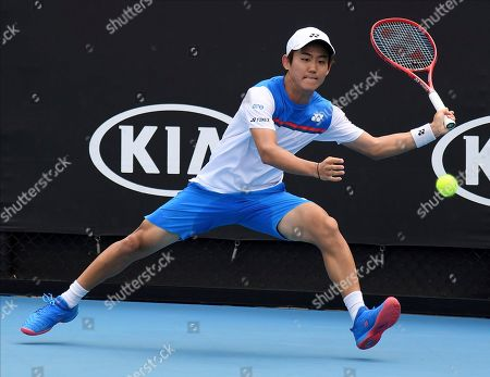 Japan's Yoshihito Nishioka runs to hit a forehand return to Serbia's Laslo Djere during their first round singles match the Australian Open tennis championship in Melbourne, Australia