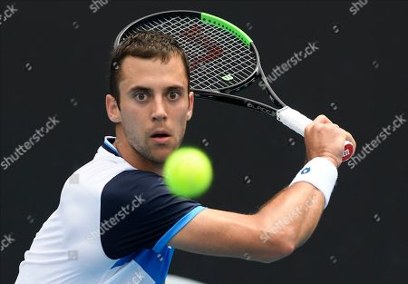 Serbia's Laslo Djere makes a backhand return to Japan's Yoshihito Nishioka during their first round singles match the Australian Open tennis championship in Melbourne, Australia