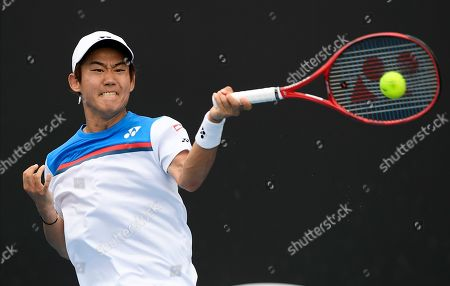 Japan's Yoshihito Nishioka makes a forehand return to Serbia's Laslo Djere during their first round singles match at the Australian Open tennis championship in Melbourne, Australia