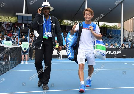 Japan's Yoshihito Nishioka, right, gestures as he leaves the court after defeating Serbia's Laslo Djere in their first round singles match at the Australian Open tennis championship in Melbourne, Australia