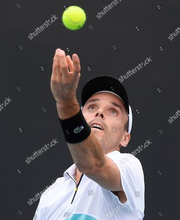 Spain's Roberto Bautista Agut serves to compatriot Feliciano Lopez during their first round singles match at the Australian Open tennis championship in Melbourne, Australia