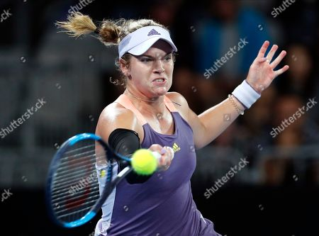 Catherine McNally of the United States makes a forehand return to Australia's Samantha Stosur during their first round singles match the Australian Open tennis championship in Melbourne, Australia