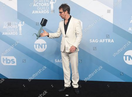 """Sam Rockwell flips his award for outstanding performance by a male actor in a television movie or miniseries for """"Fosse/Verdon"""" in the press room at the 26th annual Screen Actors Guild Awards at the Shrine Auditorium & Expo Hall, in Los Angeles"""