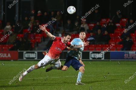 Stock Image of Liam Hogan of Salford City goes down dramatically under pressure from Accrington's Dion Charles