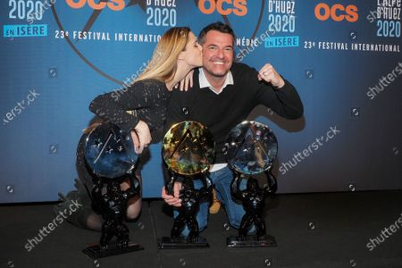 Arnaud Ducret and girlfriend Claire Francisci pose with their two awards