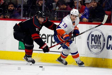 Stock Photo of Jordan Staal, Mathew Barzal. Carolina Hurricanes' Jordan Staal (11) battles with New York Islanders' Mathew Barzal (13) during the third period of an NHL hockey game in Raleigh, N.C