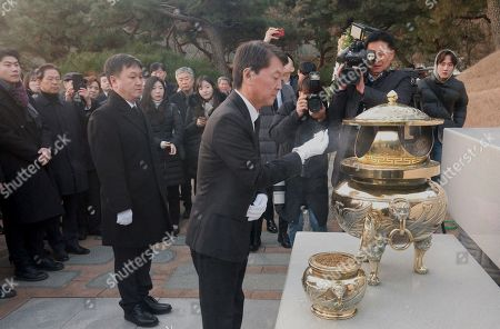 Stock Photo of Former South Korean presidential candidate and co-founder of the minor opposition Bareunmirae Party, Ahn Cheol-Soo (C) pays his respects at the grave of former South Korean President Kim Dae-Jung at the National Cemetery in Seoul.