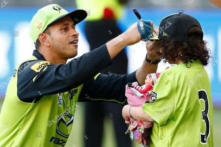 Stock Picture of Usman Khawaja of Sydney Thunder signs Grace's hat befor ethe start of the match