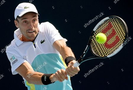 Spain's Roberto Bautista Agut makes a backhand return to compatriot Feliciano Lopez during their first round singles match at the Australian Open tennis championship in Melbourne, Australia