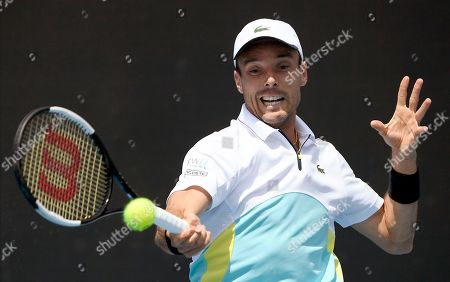 Spain's Roberto Bautista Agut makes a forehand return to compatriot Feliciano Lopez during their first round singles match at the Australian Open tennis championship in Melbourne, Australia