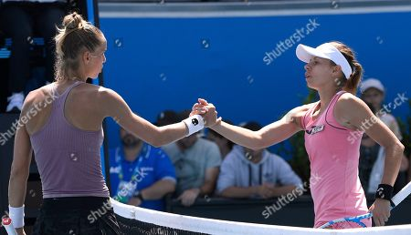 Arantxa Rus, left, of the Netherlands is congratulated by Poland's Magda Linette after winning their first round singles match at the Australian Open tennis championship in Melbourne, Australia
